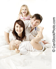 Happy family: parents playing with two kids in bed