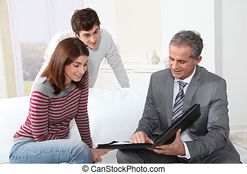 Young couple signing renting contract with real estate agent