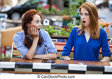 Two girls gossiping in the cafe