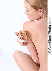 Beautiful woman using massage brush