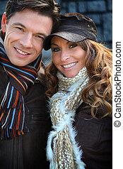 Portrait of happy couple wearing scarves in winter time