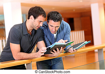Young men looking at agenda in building hall