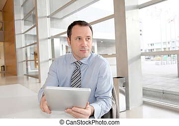 Businessman sitting in the office with electronic tablet