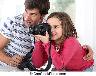 Father teaching little girl how to use camera