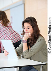 Teenage girl at school using electronic tablet