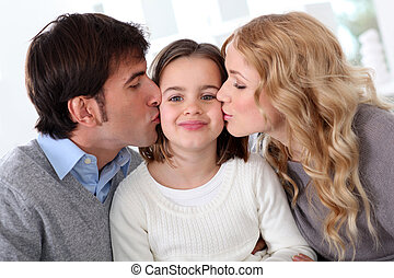 Portrait of parents kissing their daughter