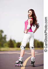 woman roller skating - happy young brunette woman roller...