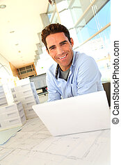 Smiling architect sitting in office