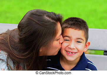 Mom kissing young son on cheek - Loving mother kissing her...