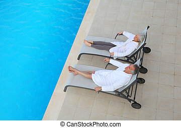 Senior couple relaxing in long chairs