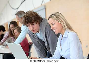 Teacher and teenage boy in front of laptop computer
