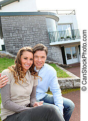 Couple sitting in front of their new home