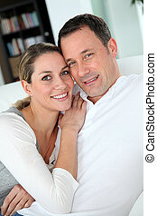 Portrait of couple relaxing at home in sofa