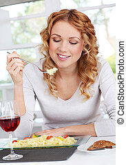 Woman eating pasta for dinner