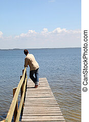 Man on a pontoon by a lake in summer