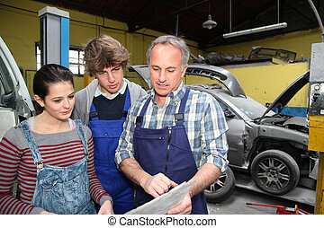 Teenagers in professional training with garage owner