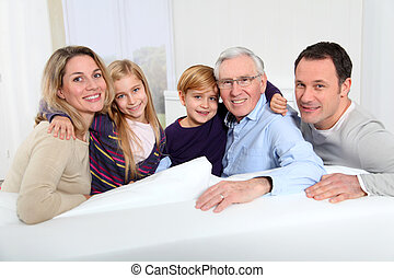 Portrait of happy family sitting in sofa at home