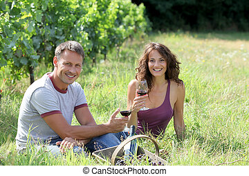 Couple of winegrowers drinking wine in vineyard
