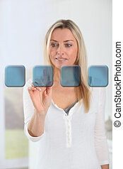 Blond woman touching virtual screen