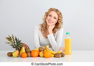 Smiling blond woman sitting with fruits on table