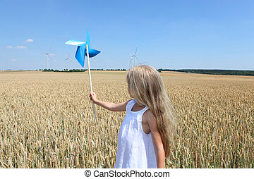 Little girl in wheat field holding wind wheel
