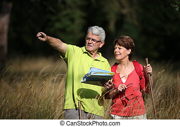 Senior couple rampling in countryside with map