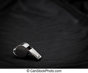 Referee whistle on black background