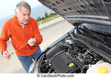 Senior man checking car motor levels