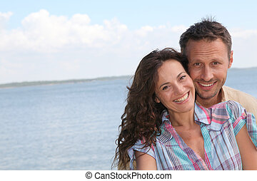 Closeup of loving couple standing on a pontoon by a lake