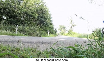 cycling in a country road - cyclist going around a bend in a...