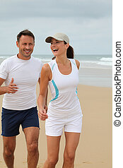 Couple jogging on a sandy beach