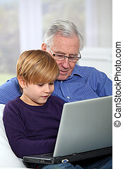 Elderly man with grandkid using laptop computer