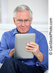 Elderly man connected on internet with electronic tab