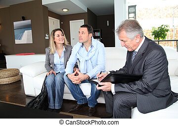 Couple with real-estate agent signing home investment...