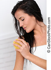 Attractive woman using natural sponge
