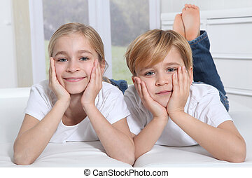 Blond children laying in sofa with hands on chin