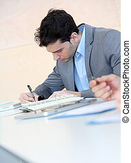 Young man filling in application form