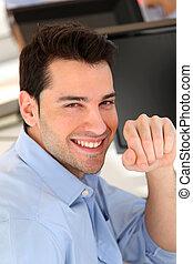 Smiling trader in front of desktop computer
