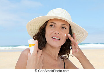 Beautiful woman at the beach putting sunscreen on her body
