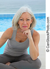 Senior woman doing exercises by a swimming-pool