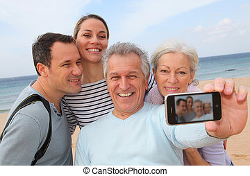 Family taking picture at the beach