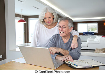 Senior couple surfing on internet at home