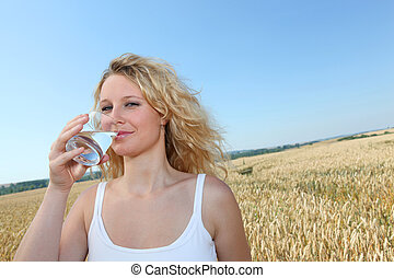 Beautiful blonde woman, drinking water from glass