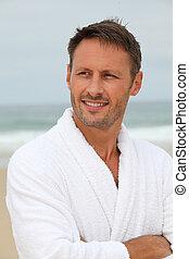 Man with bathrobe on the beach