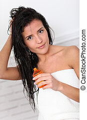 Attractive young woman holding scented oil bottle