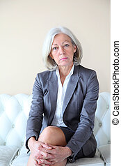 Senior woman in grey suit sitting in white sofa