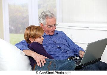 Elderly man with grandkid using laptop computer
