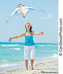 Woman on beach playing with a colorful kite - Young cute...