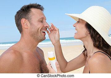 Woman putting sunblock on her boyfriend's nose