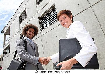 Vendeurs, secousse, mains, devant, bureau, bâtiment